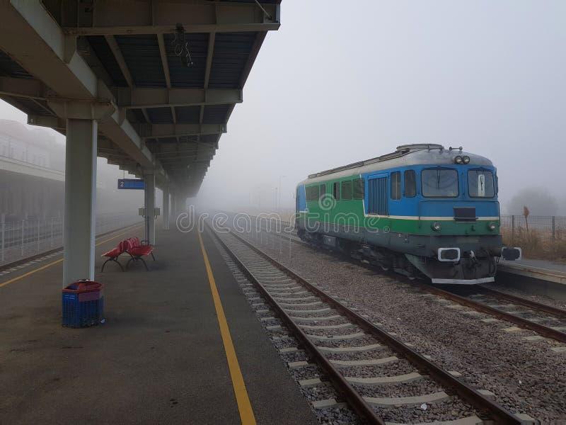 Locomotief gestationeerd in het treinstation op een foggy herfstdag royalty-vrije stock afbeeldingen