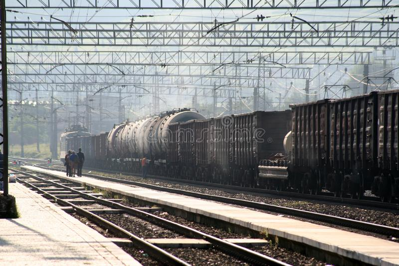 Locomotief met een goederentrein bij een station stock foto