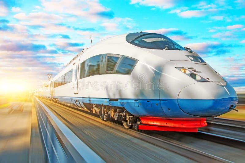 Locomotiva do passageiro do trem de alta velocidade no movimento na estação de trem no por do sol com um céu pitoresco bonito fotos de stock