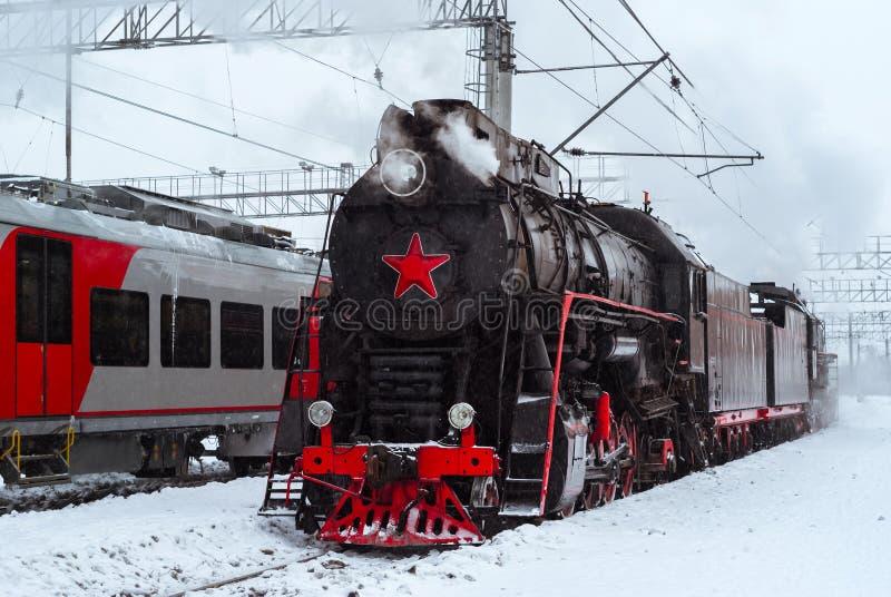Locomotiva a vapore e supporto multiplo moderno del treno vicini alla stazione fotografie stock libere da diritti