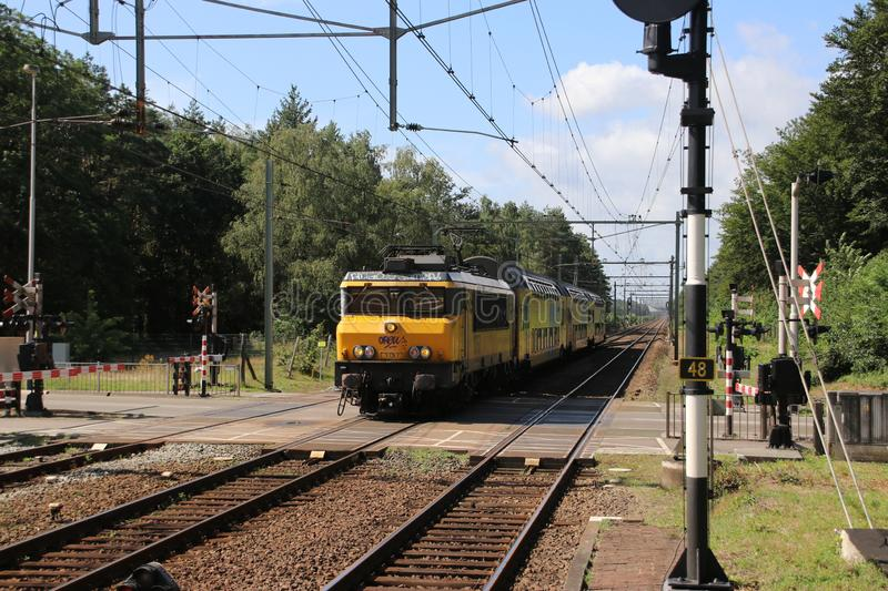 Locomotive and DDZ local commuter double decker train on track at station `t Harde in the Netherlands. stock image