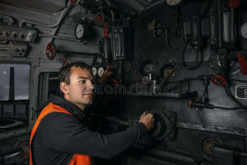 Locomotive driver in the workplace in the cabin of the locomotive controls the levers royalty free stock photos