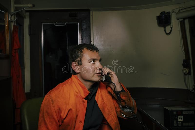 Locomotive driver in the workplace in the cabin of the locomotive is talking on the old wired telephone.  stock photos
