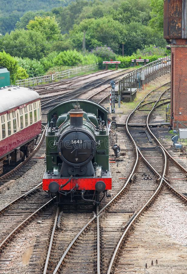 A 0.6.0 locomotive shunting past some carriages. Photo of a 0.6.0 locomotive shunting past some carriages royalty free stock photography