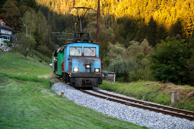 Locomotive. A vintage electric train running on a sunlit Alpine track. The engine is brightly blue coloured. A sense of nostagia of when life had a slower pace stock photo