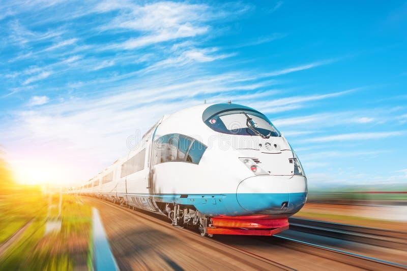Locomotora de alta velocidad del pasajero del tren rápido en el movimiento en el cielo azul pintoresco hermoso del ferrocarril imagen de archivo