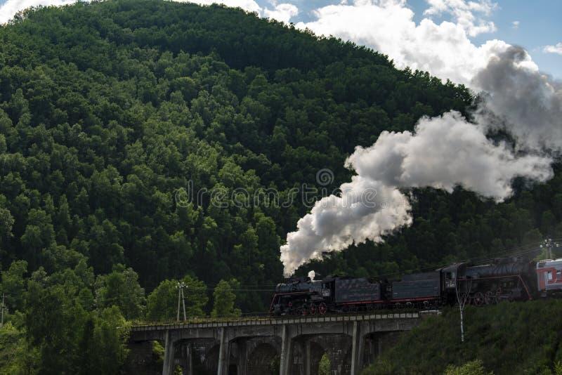 Locomotora de vapor que se mueve a lo largo de un ferrocarril siberiano viejo foto de archivo libre de regalías