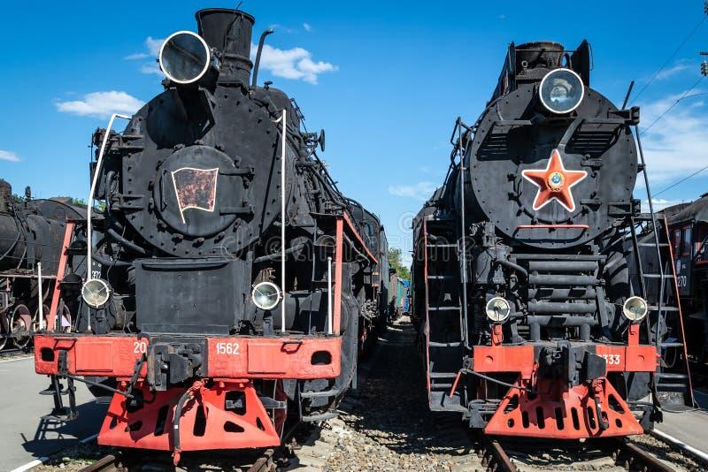 Locomotora de vapor vieja al lado de una plataforma del ferrocarril Tren retro imagen de archivo