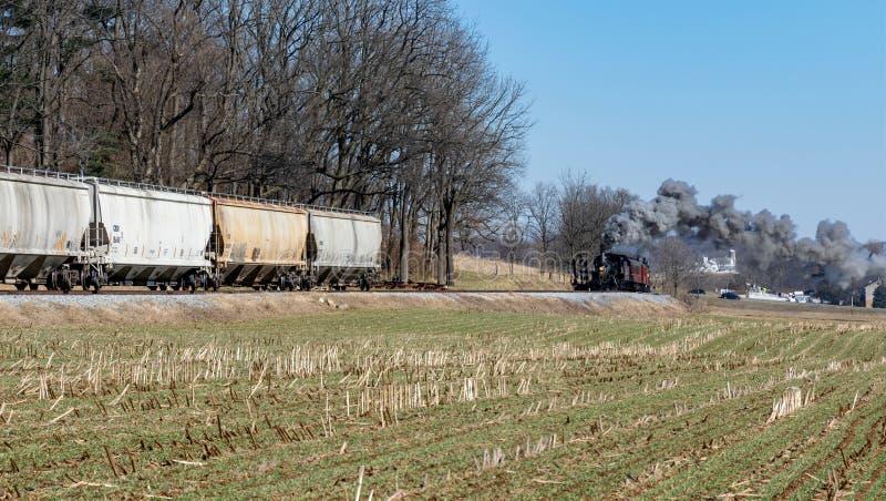 Locomotora de vapor y fletar los coches de la tolva en el campo de Amish fotografía de archivo