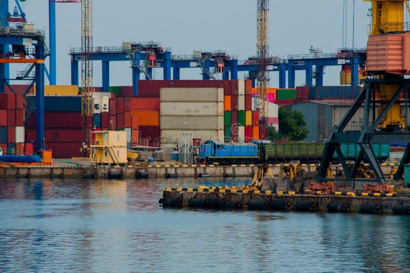 Locomotora eléctrica azul entre las grúas en puerto imágenes de archivo libres de regalías