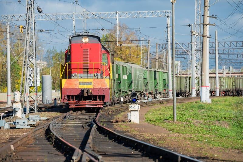 Locomotora roja y coches de carga verdes fotografía de archivo libre de regalías