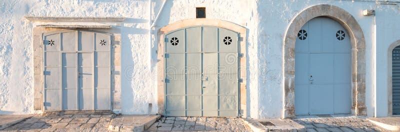 Locorotondo, Апулия, южная Италия Панорамное фото 3 широких дверей в пастельных цветах стоковое фото