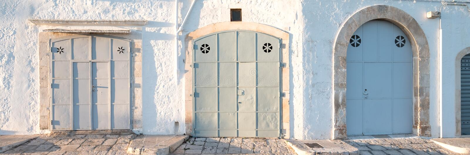 Locorotondo, Puglia, Southern Italy. Panoramic photo of three wide doors in pastel colours. Locorotondo, Puglia, Southern Italy. Panoramic photo of three wide stock photo