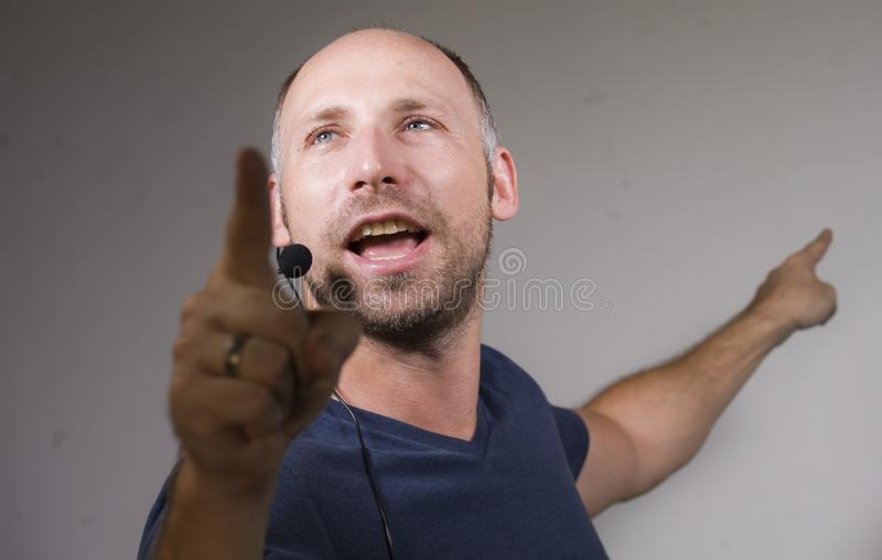 Locutor atractivo y confiado feliz del hombre de negocios con las auriculares que dan el entrenamiento de la conferencia que entr imagen de archivo