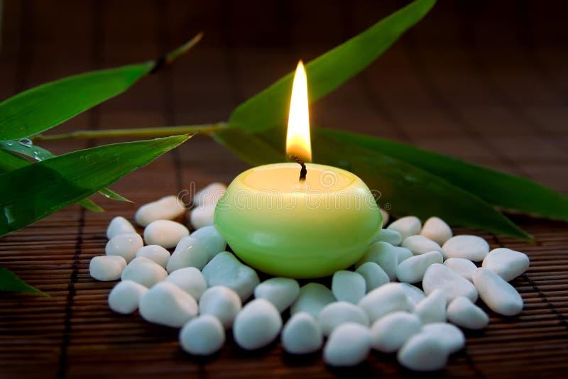 Lodernde Kerze mit Steinen lizenzfreies stockfoto