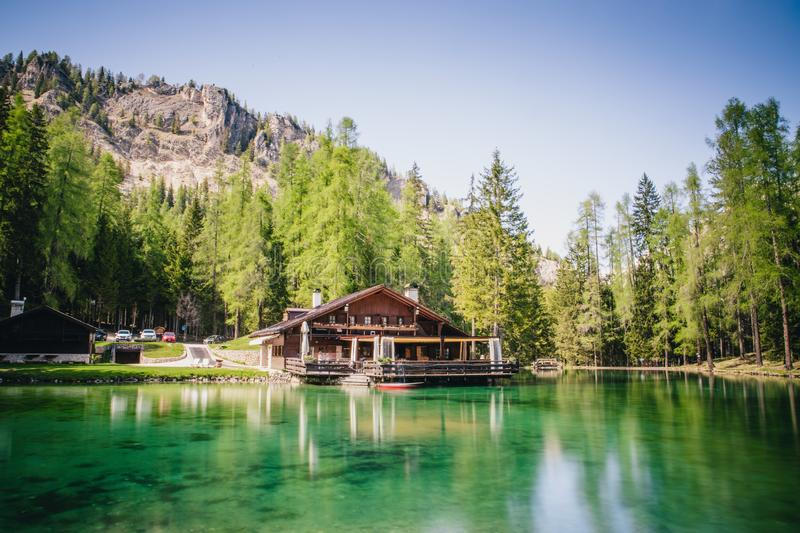 The lodge over the turquoise waters of Lago Ghedina, an alpine lake in Cortina D`Ampezzo, Dolomites, Italy royalty free stock image