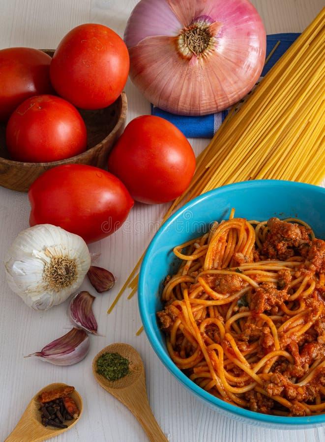 Lodlinje för bästa sikt av spagetti som är bolognese med dess ingredienser, tomat, lök, vitlök och kryddor arkivbilder