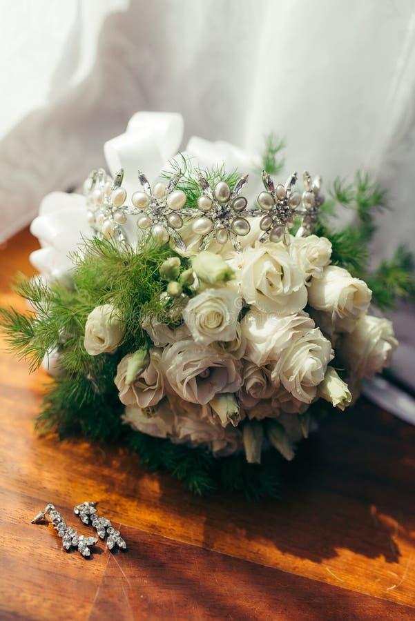 Lodlinjeskottet av de långa silverörhängena med diamanter som ligger nära bröllopbuketten av vita rosor med håret royaltyfria foton