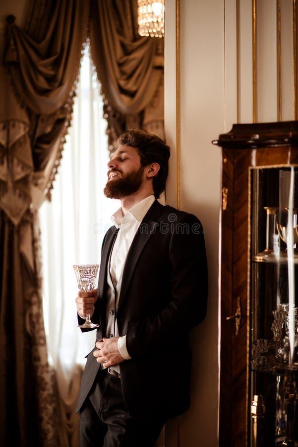 Lodlinjeskottet av den nöjda skäggiga unga affärsmannen bär svart formellt dräkthållexponeringsglas och dricker drycken, står in arkivbilder