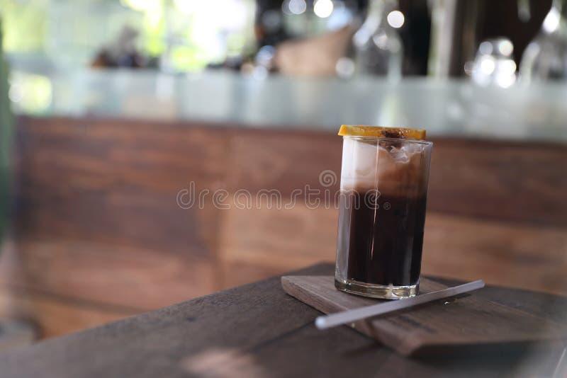 Lodowa czarna kawa z pomarańcze na drewnianym tle zdjęcie royalty free