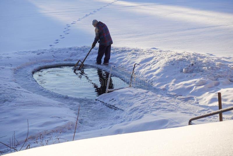 Lodowa dziura w jeziorze w zimie wyposaża z drabiną dla wszczynać Mężczyzna czyści lodowej dziury zdjęcia royalty free