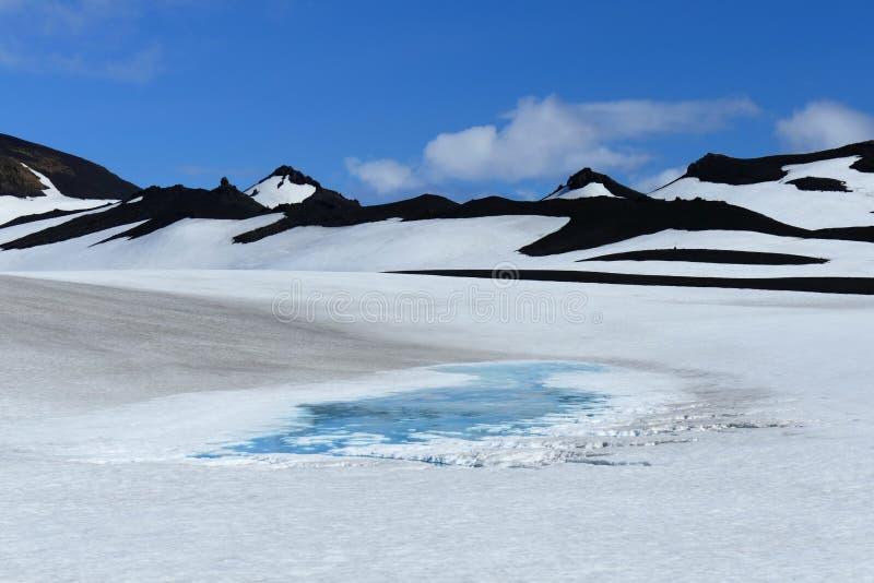 Lodowaty błękitny jezioro po środku czarnej skały i biały śniegu krajobraz na Fimmvörduhals przełęczu, Iceland zdjęcie royalty free