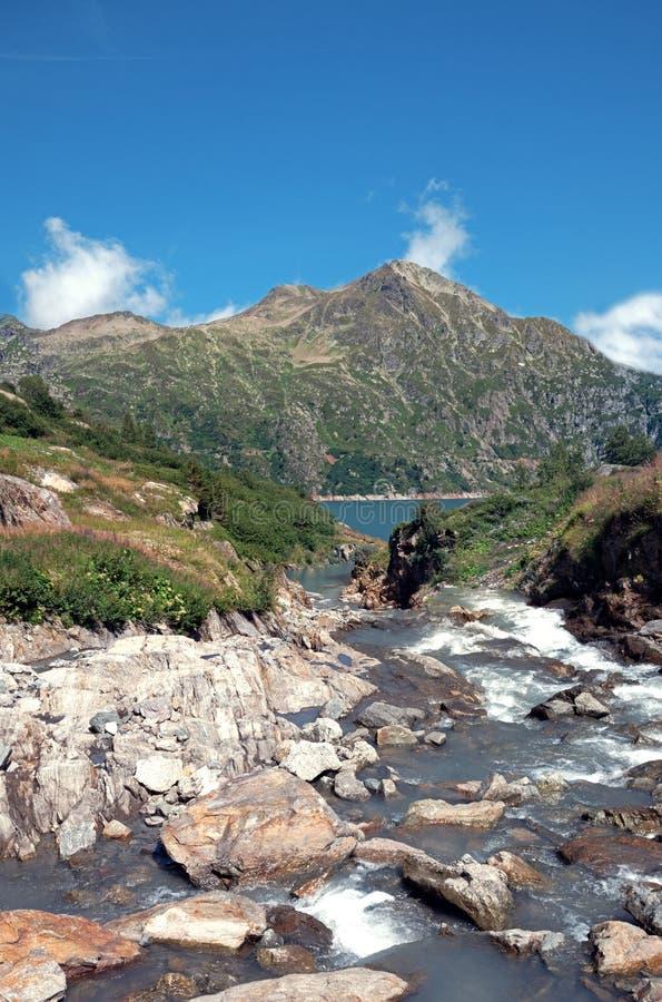Lodowiec topi rzecznych przepływy nad skałami w jeziorną obubrzeżną wysokość w wysokogórskich szczytach Szwajcaria zdjęcie royalty free