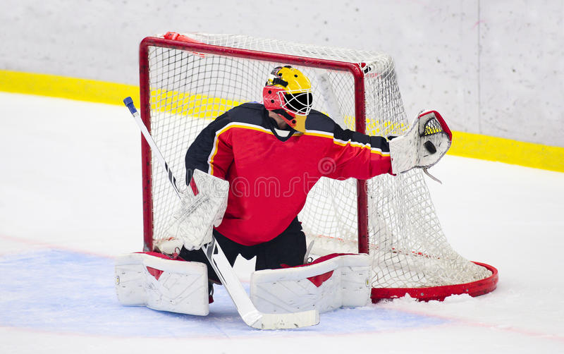 Lodowy hokej - bramkarz łapie krążek hokojowego obraz royalty free