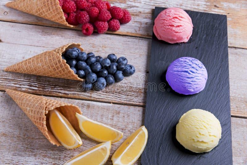Lody dobierać piłki z cytryny malinową borówką na drylują powierzchnię z kawałkami owoc Wyśmienicie świeżych owoc lody obrazy royalty free