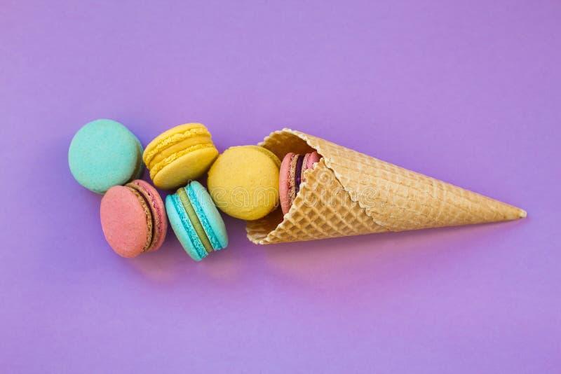 Lody gofra rożek z kolorowym macaron lub macaroon na fiołkowego purpurowego tła odgórnym widoku Kolorowi cukierków kolory obrazy royalty free