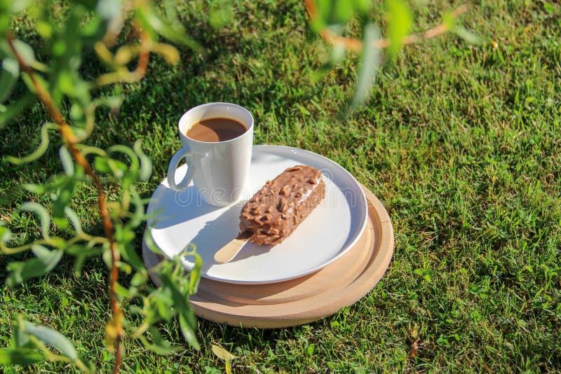 Lody i filiżanka kawy słuzyć na trawie na gorącym letnim dniu obraz stock