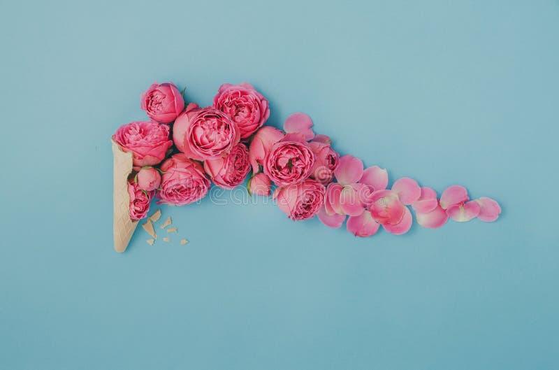 Lody rożek z różowymi różami na błękitnym tle obraz stock