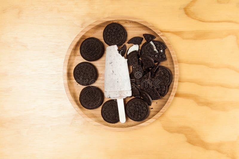 Lody - smakowitego i odświeżającego popsicle sosowani ciastka i śmietanka, fotografia na drewnianym tle zdjęcie royalty free