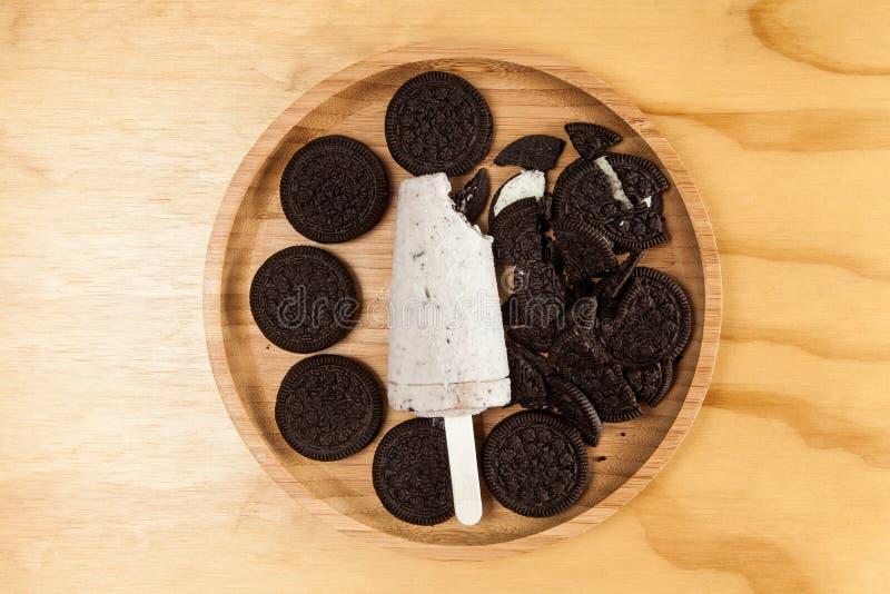 Lody - smakowitego i odświeżającego popsicle sosowani ciastka i śmietanka, fotografia na drewnianym tle zdjęcia royalty free