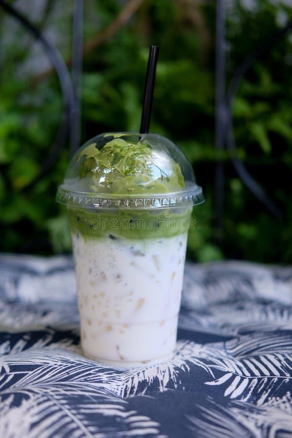 Lody zielonej herbaty pławik na świeżym mleku w plastikowym szkle zdjęcie stock