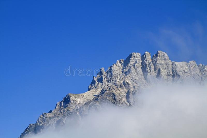 Loferer Steinberge in Austria. The craggy peaks of the Loferer Steinberge rise above the swath of the morning mist stock photos