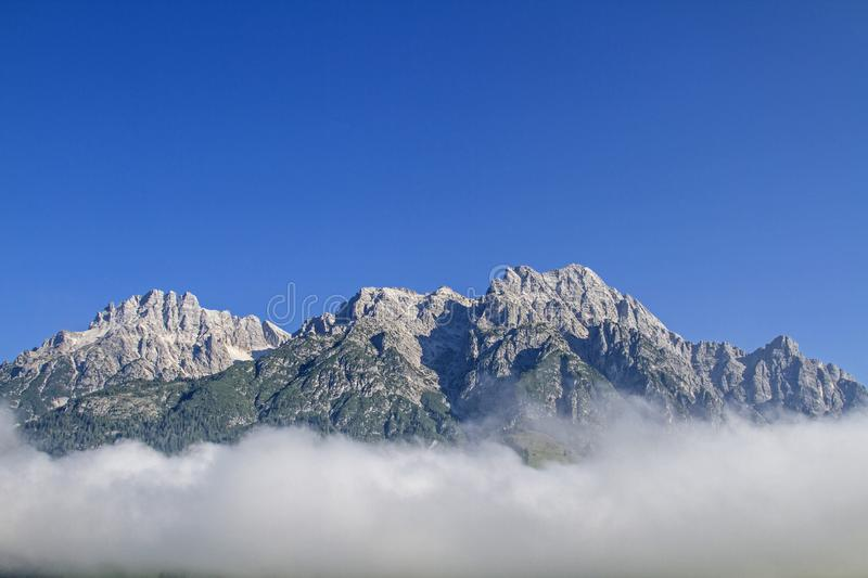 Loferer Steinberge in Austria. The craggy peaks of the Loferer Steinberge rise above the swath of the morning mist stock image