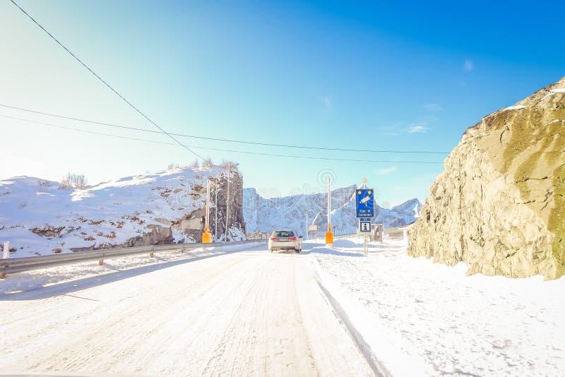 LOFOTEN,挪威, 2018年4月, 10日:冻街道室外看法有照相机录音速度的一个情报标志的和 库存图片