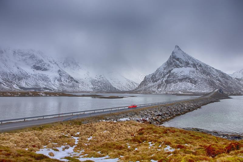 Lofoten Islands In Norway. Red Noticable Car Passing by Fredvang Bridge At Lofoten Islands In Winter Time in Norway. Horizontal Image Orientation stock image