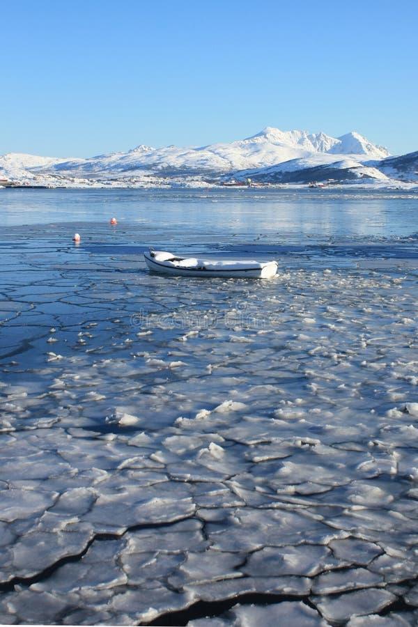 Lofoten's ice prison. Boat emprisoned by the ice in the fjord of busknes, Lofoten islands stock image