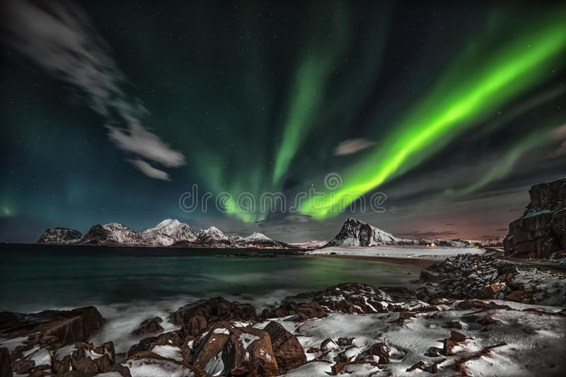 A northern lights performance at StorSandnes in Lofoten islands. Lofoten is situated just beneath the auroral oval, a belt of light that encircles the stock photo