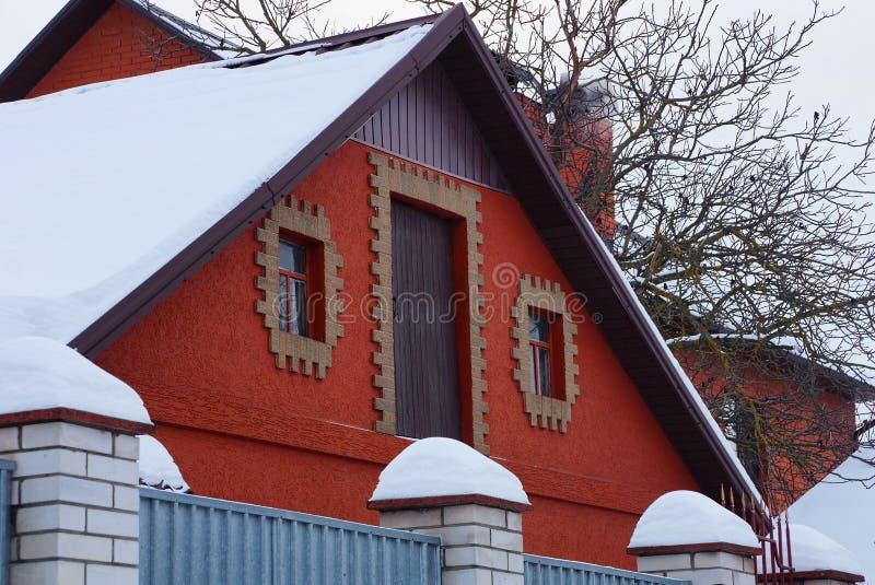 Loft av en röd landsladugård med en dörr och vit snö för fönster och på taket bak staketet royaltyfria foton