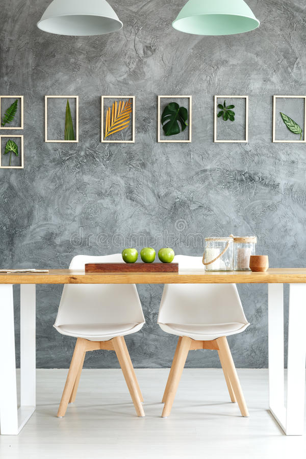 Loft with botanic decorations. On textured wall and wooden table with two white chairs royalty free stock photo