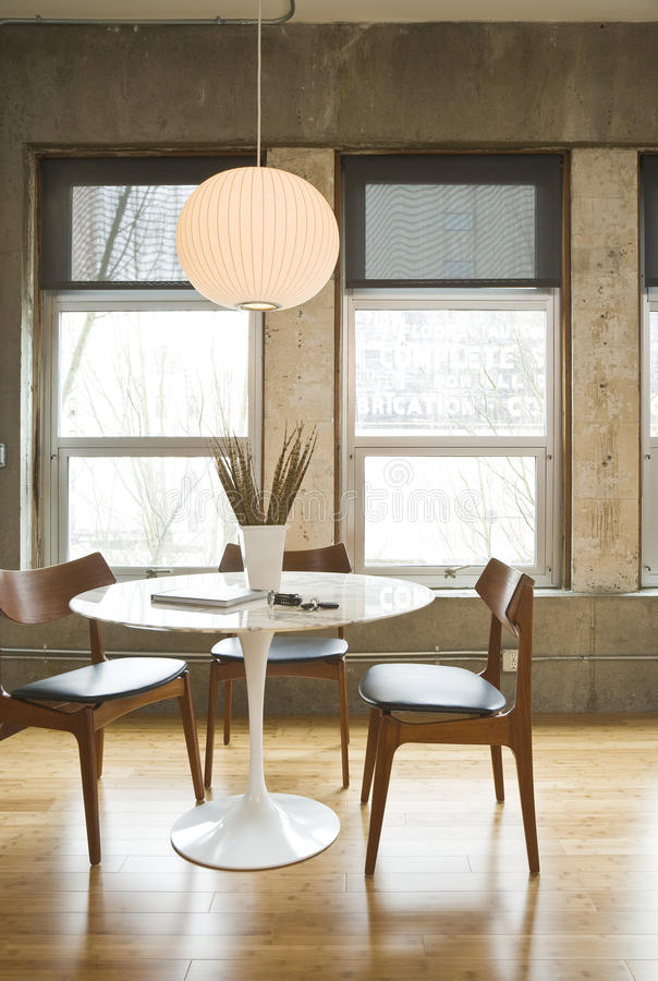 Loft Dining Room. Dining room table and chairs in a modern loft setting. Vertical shot royalty free stock image