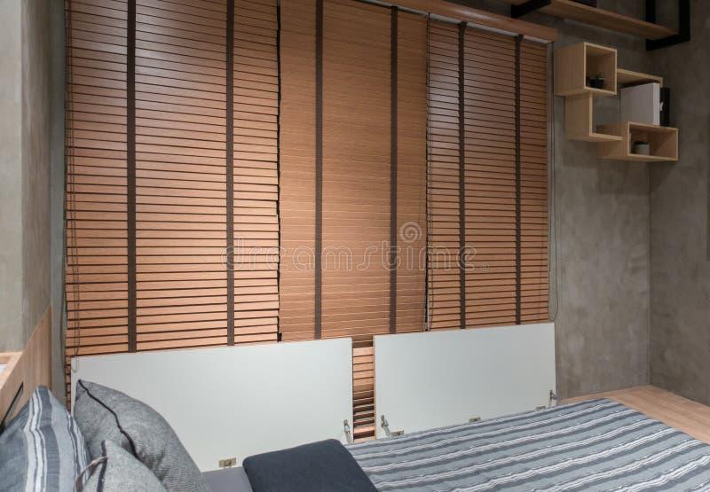 Loft el dormitorio con la cama cerca de la pared de ladrillo y de la cortina de madera fotos de archivo libres de regalías
