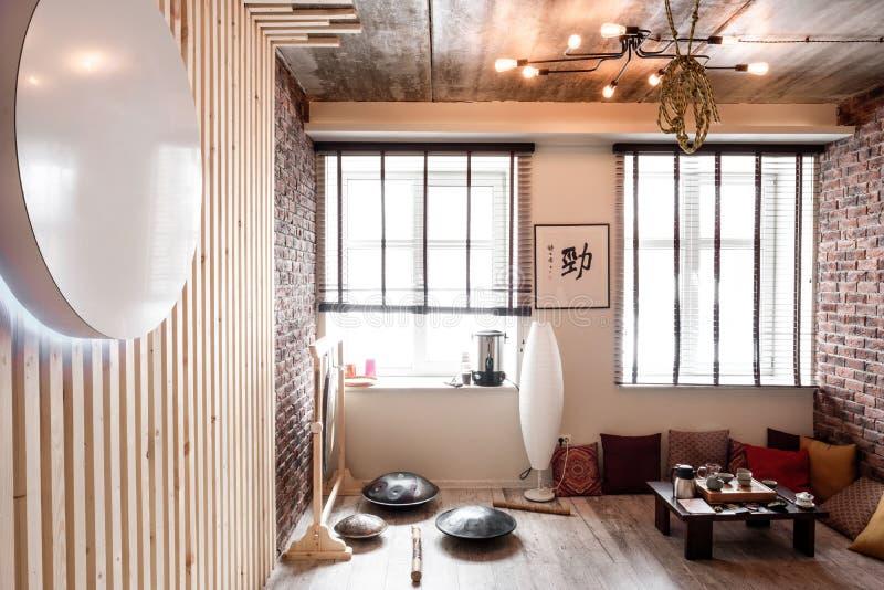 Loft el sitio para la aptitud y la relajación, la relajación con las paredes de ladrillo y las ventanas, gimnasio, té imagenes de archivo
