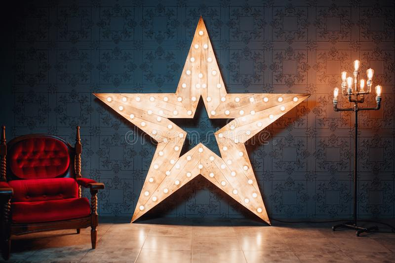 Loft room. Beautiful decor. Wooden star with lamps and leather armchair in a dark room. royalty free stock photo