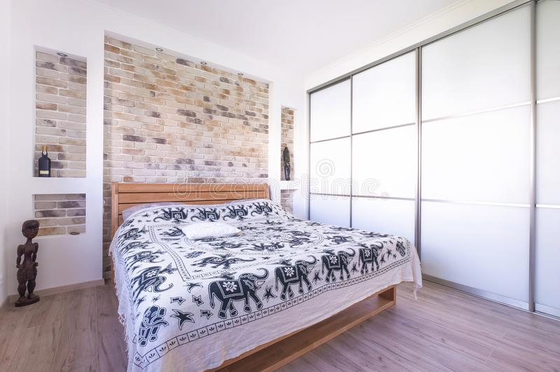 Loft style designed bedroom with double bed, build in wardrobe,. Brick wall and travel souvenirs stock image