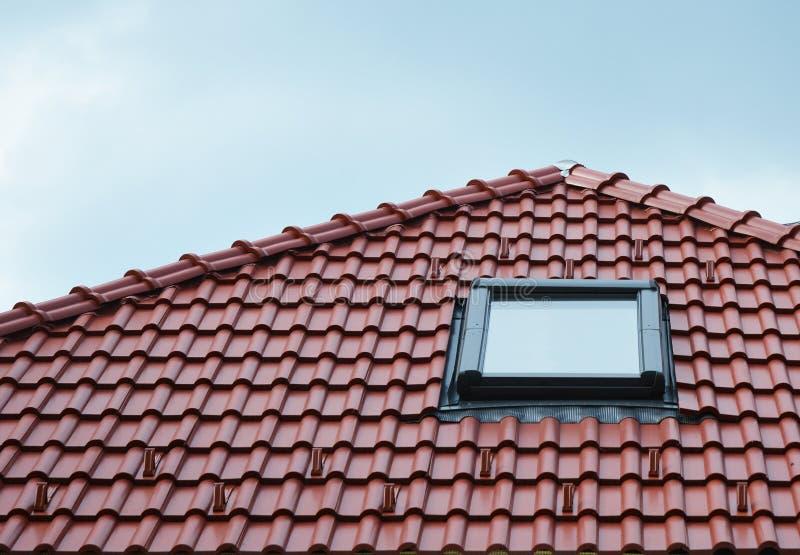 Lofttakfönsterfönster på röda det utomhus- hustaket för keramiska tegelplattor Lofttakfönster returnerar yttre designidéer royaltyfri foto