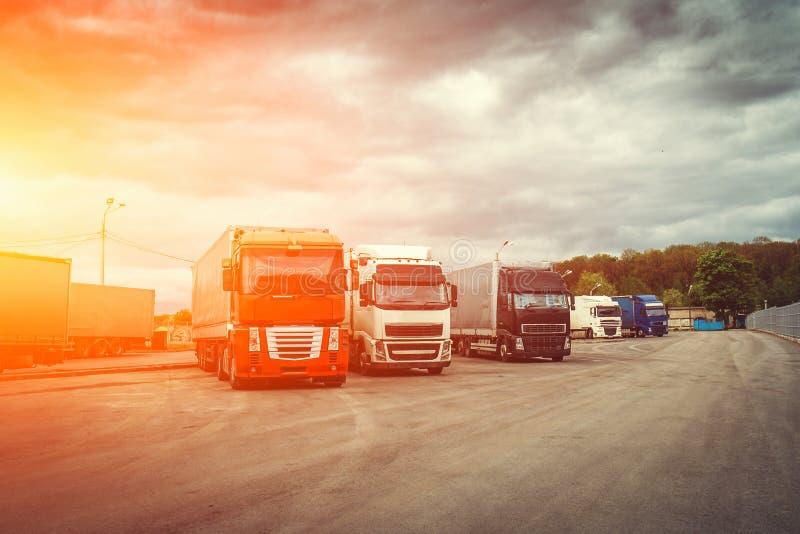 Logístico e transporte o conceito, caminhões do recipiente para a entrega da carga no tempo do por do sol, transporte industrial  fotografia de stock royalty free